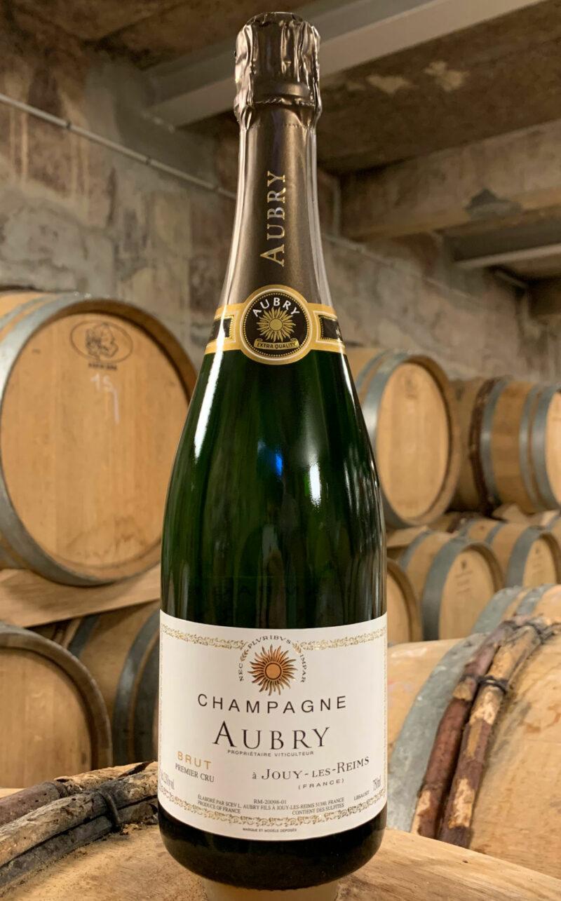 Photo d'une bouteille de Champagne Aubry Brut prise dans la cave aux côtés des fûts en chêne à Jouy-Les-Reims