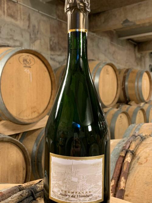 Photo d'une bouteille de Champagne Aubry de Humbert prise dans la cave aux côtés des fûts en chêne à Jouy-Les-Reims