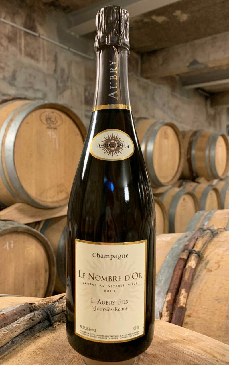 Photo d'une bouteille de Champagne Aubry Le Nombre d'Or Brut prise dans la cave aux côtés des fûts en chêne à Jouy-Les-Reims