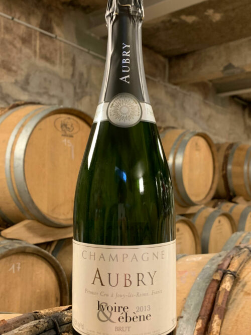 Photo d'une bouteille de Champagne Aubry Ivoire et Ébène prise dans la cave aux côtés des fûts en chêne à Jouy-Les-Reims