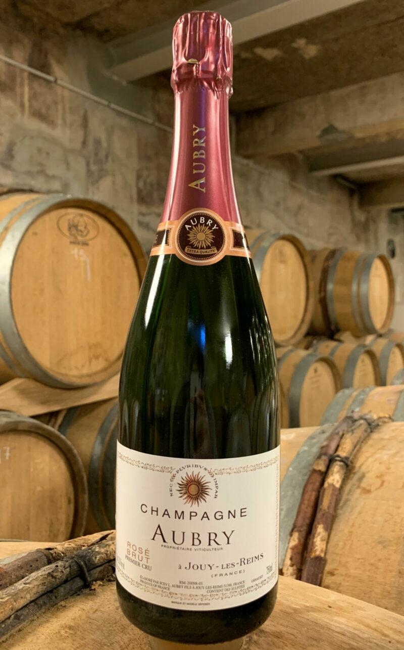 Photo d'une bouteille de Champagne Aubry Rosé prise dans la cave aux côtés des fûts en chêne à Jouy-Les-Reims