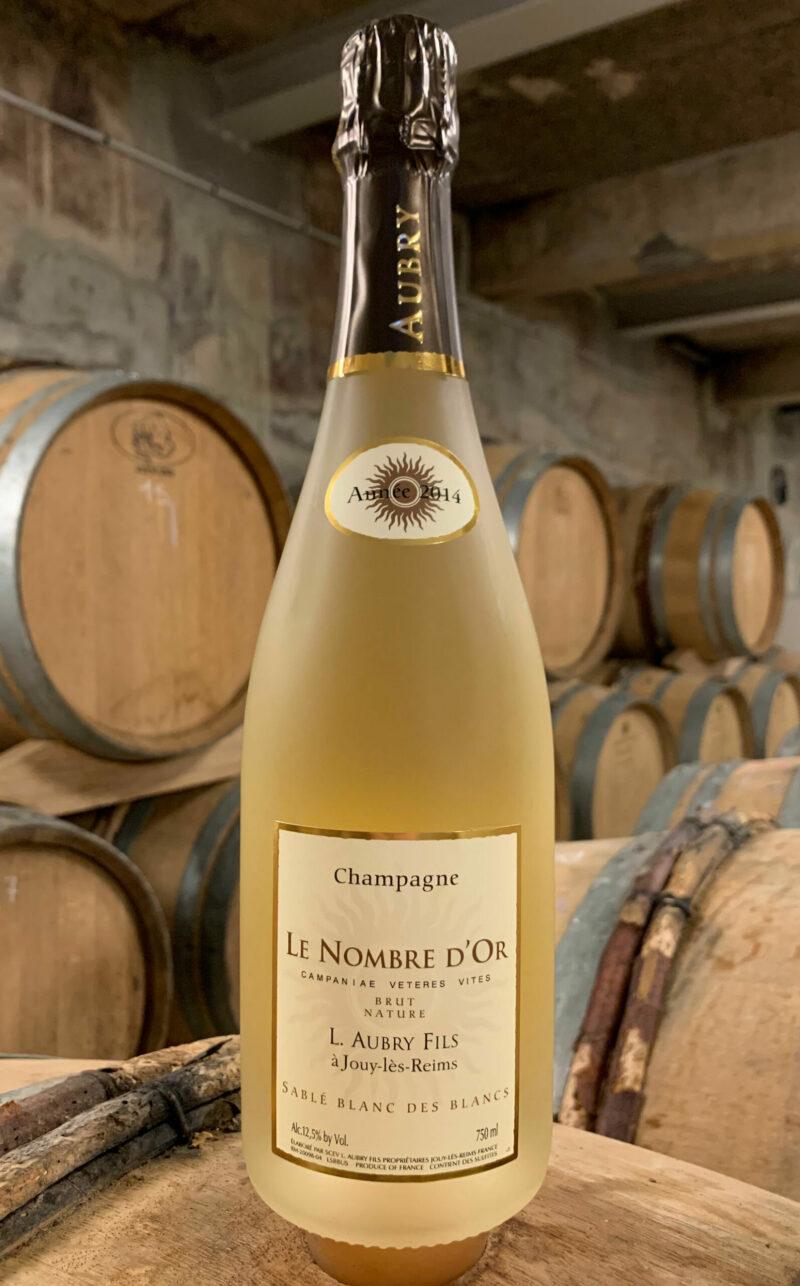 Photo d'une bouteille de Champagne Aubry Le Nombre d'Or Sablé Blanc des Blancs prise dans la cave aux côtés des fûts en chêne à Jouy-Les-Reims