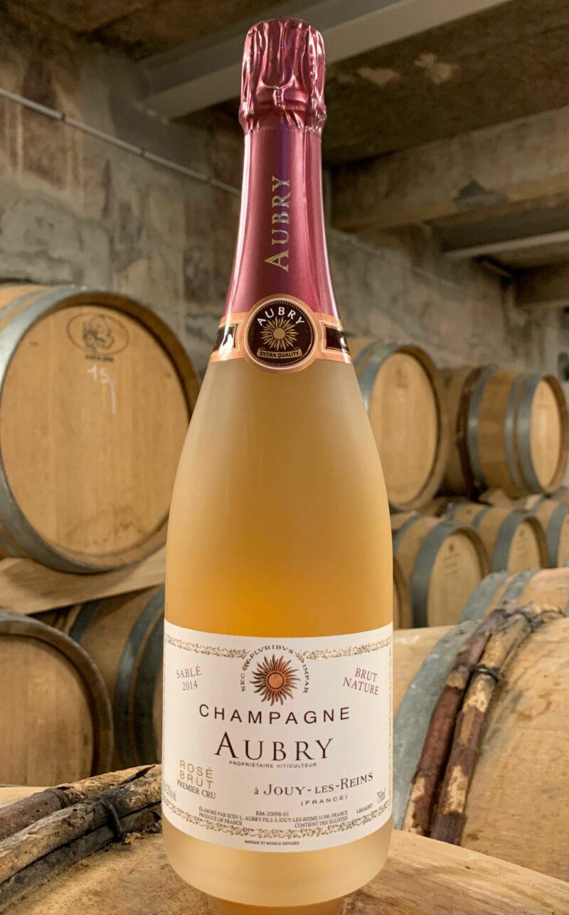 Photo d'une bouteille de Champagne Aubry Sablé Rosé prise dans la cave aux côtés des fûts en chêne à Jouy-Les-Reims
